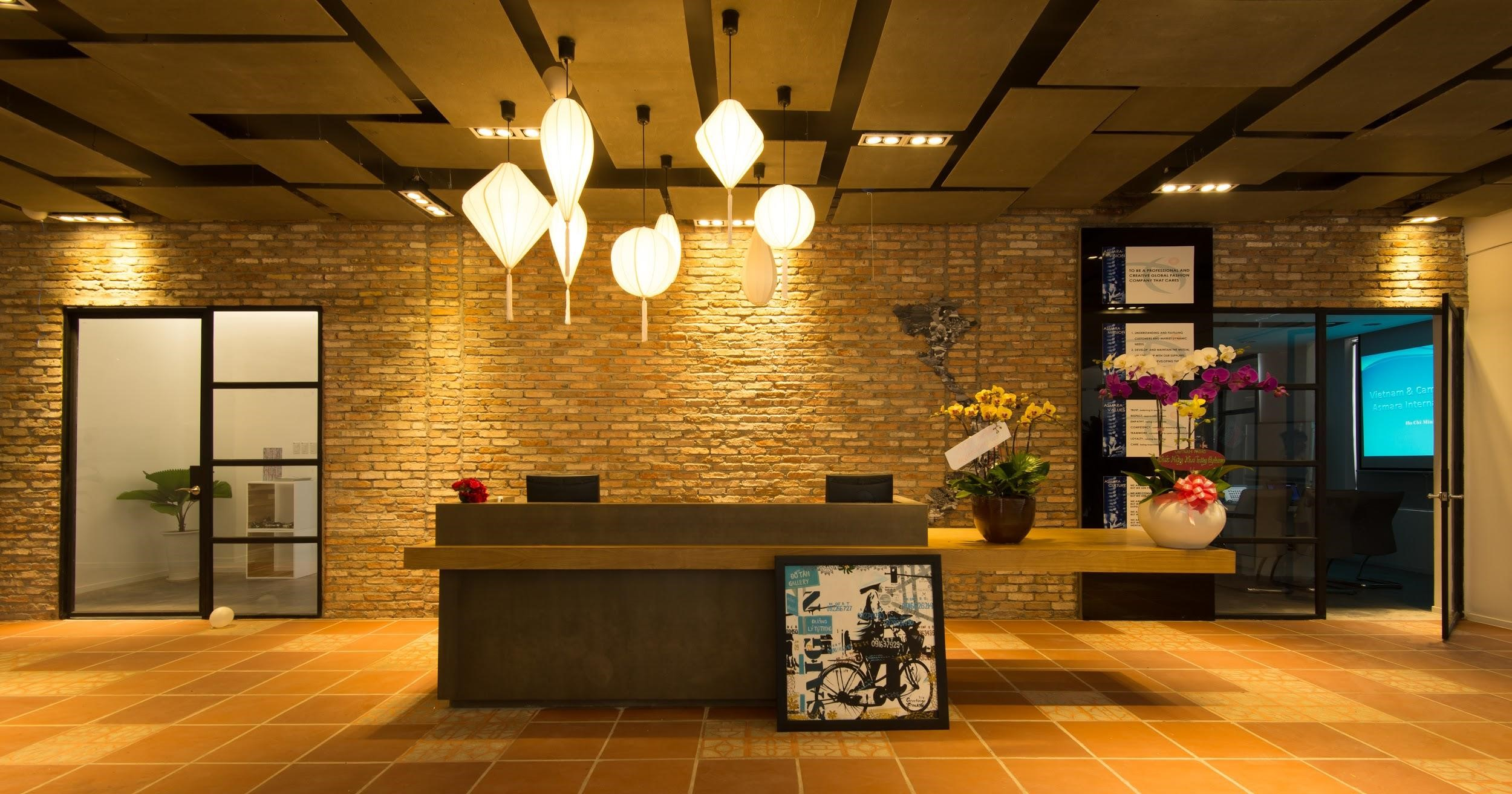 The reception in deep colours underneath lantern lights generates a cosy tone for Asmara office