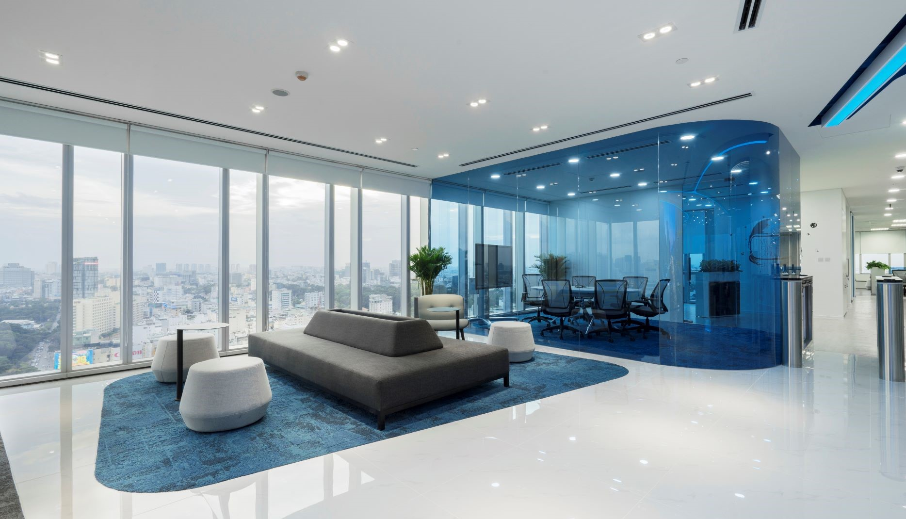 A spacious lobby with blue carpet and transparent glass wall of the meeting room