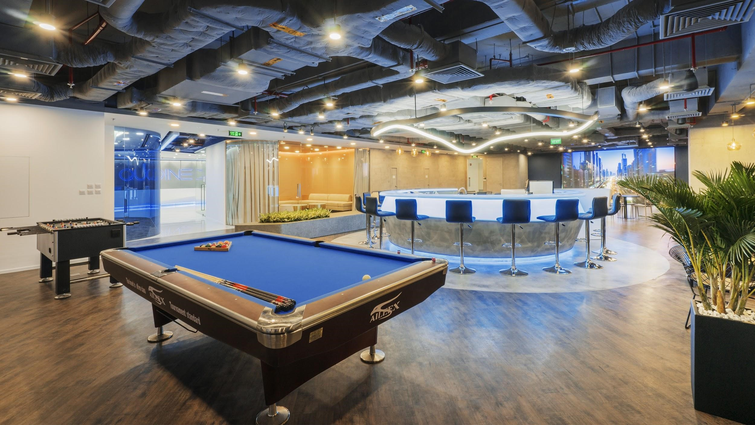The billiard lounge next to a bar with blue light brings comfort to the employees
